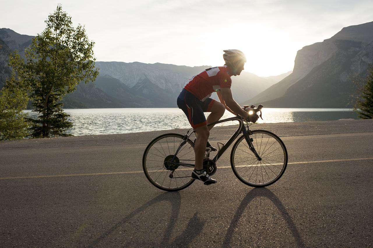 Man riding bike on road alongside a lake