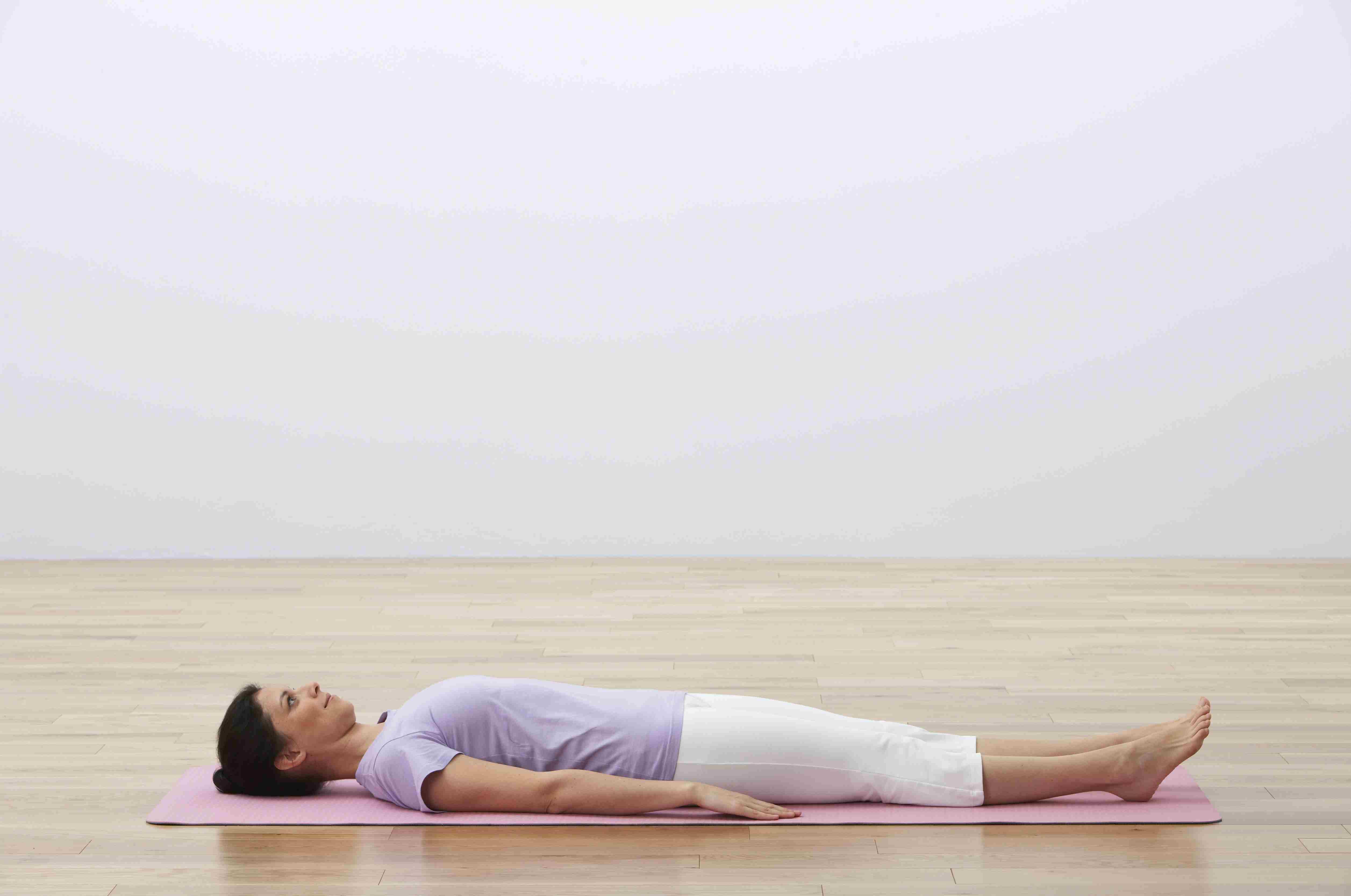 Mujer acostada de espaldas sobre una colchoneta de ejercicios, vista lateral