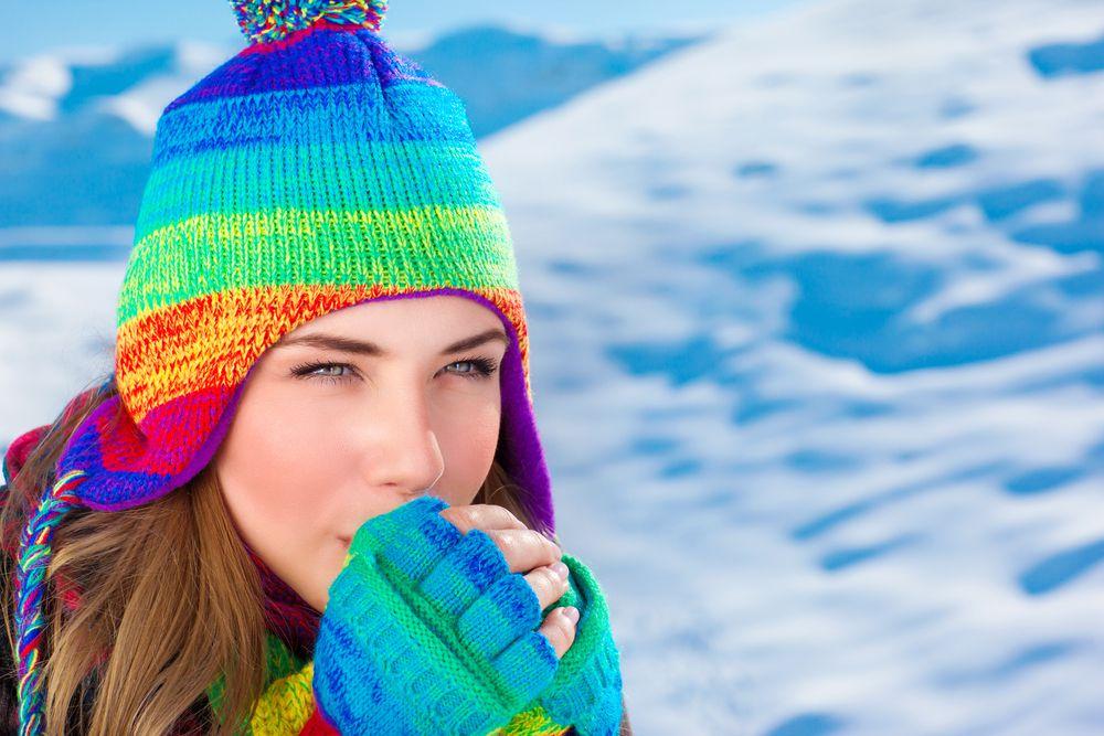 Mujer con sombrero y guantes en clima frío.