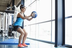 Woman exercising with medicine ball at the gym