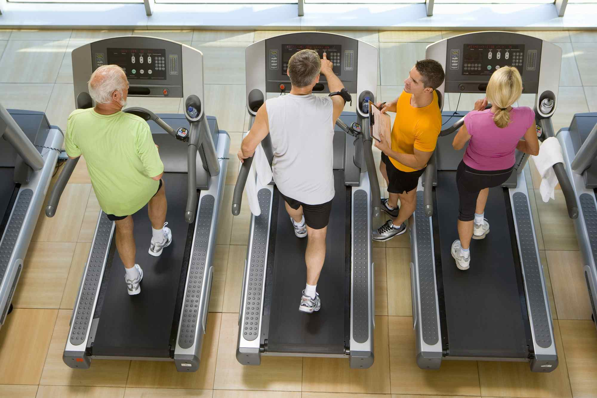 People on Treadmills in Gym with Coach