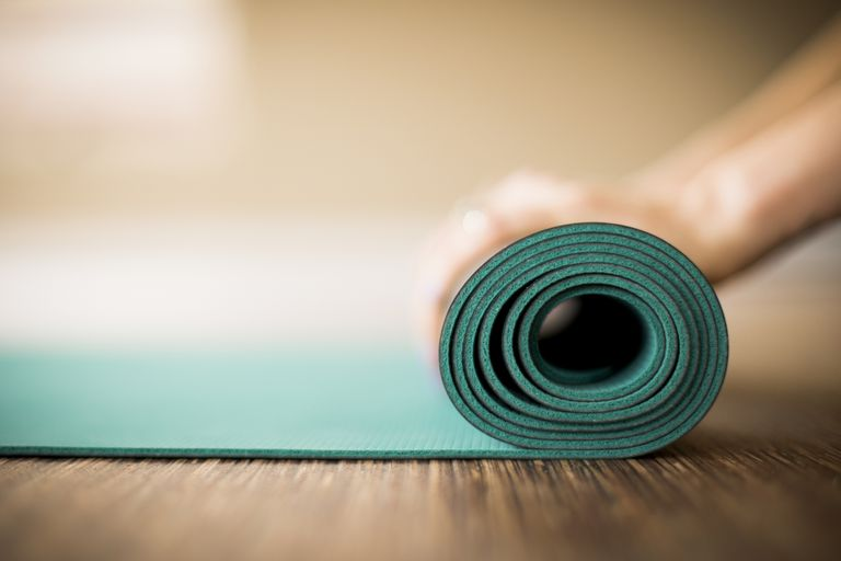 Person rolling a pilates mat