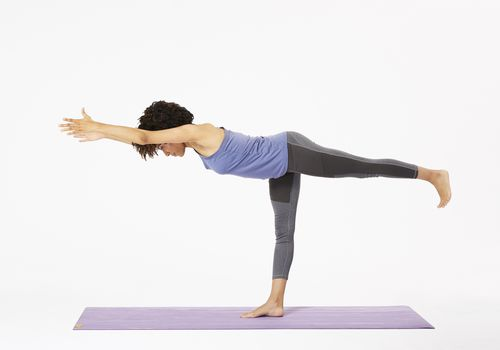 Woman on yoga mat doing warrior III pose