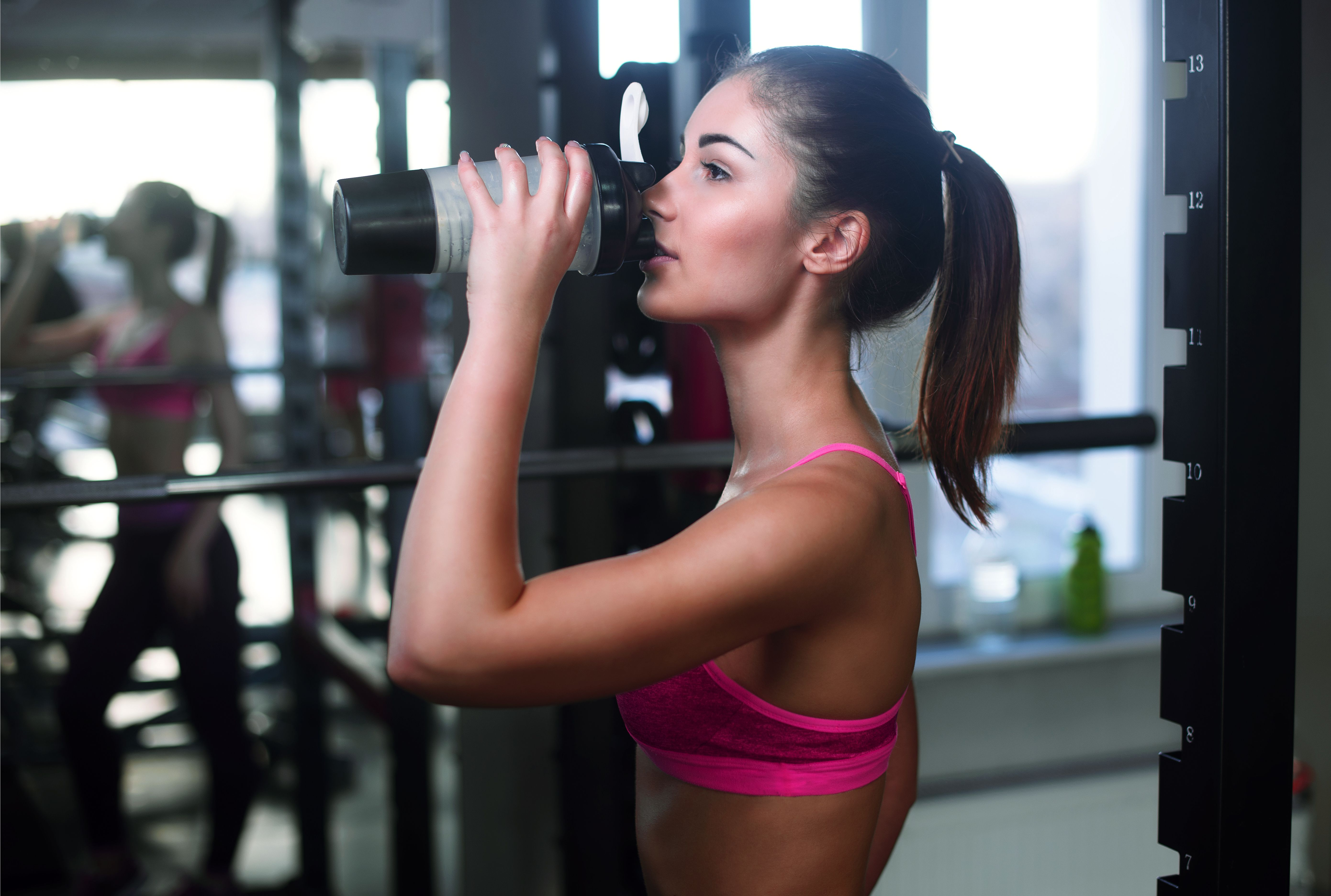 young woman drinking BCAAs from shaker bottle in gym