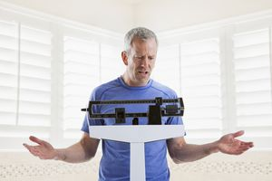 Frustrated man looking at his weight on a scale