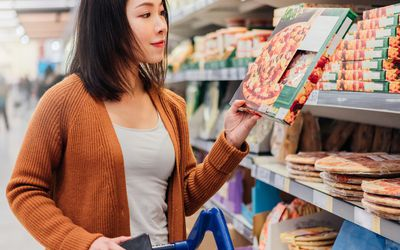 asian american woman reading a pizza box at the grocery store