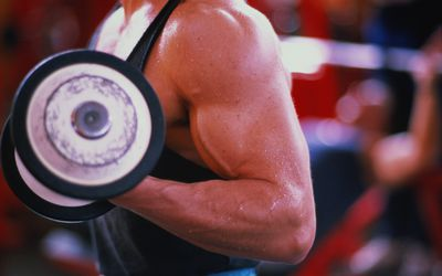 Young man exercising in gym, using dumbbell, mid section, close-up