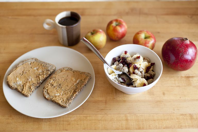 A top down view of a healthy breakfast bowl of cranberries, almonds, Greek yogurt and bananas, also apples, toast with peanut butter and a cup of coffee.