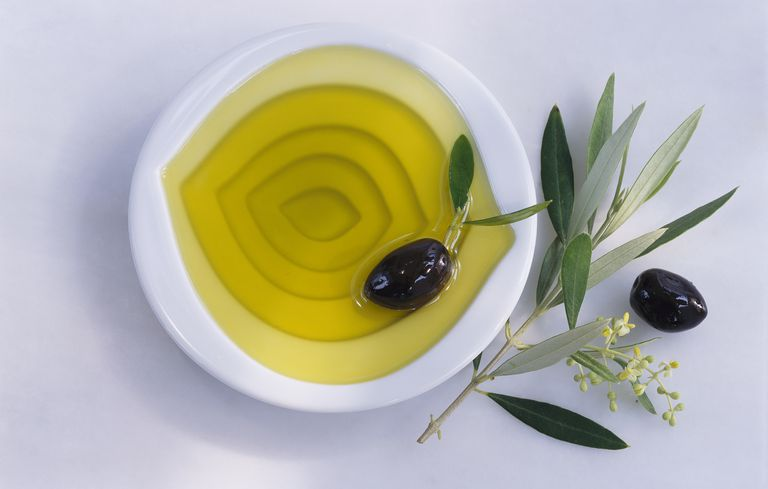 bowl of olive oil with olives and olive leaves