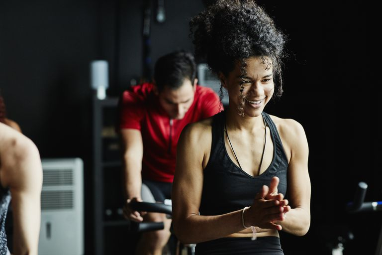 Woman laughing during indoor cycling class in fitness studio