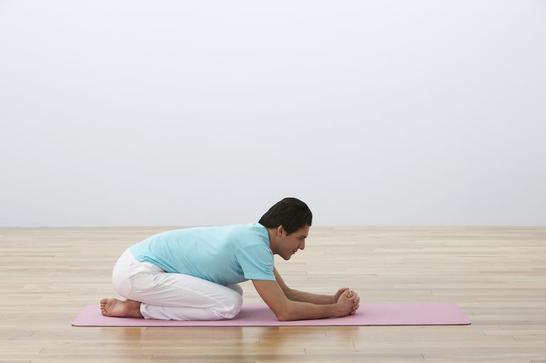 Man kneeling on exercise mat, leaning forward, side view