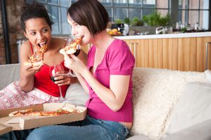 two women eating pizza and drinking wine
