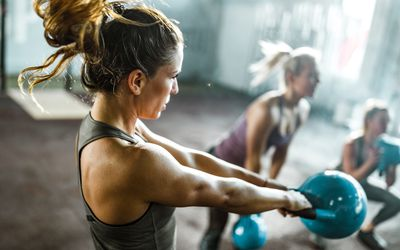 Athletic woman exercising with kettle bell on a class in a health club.