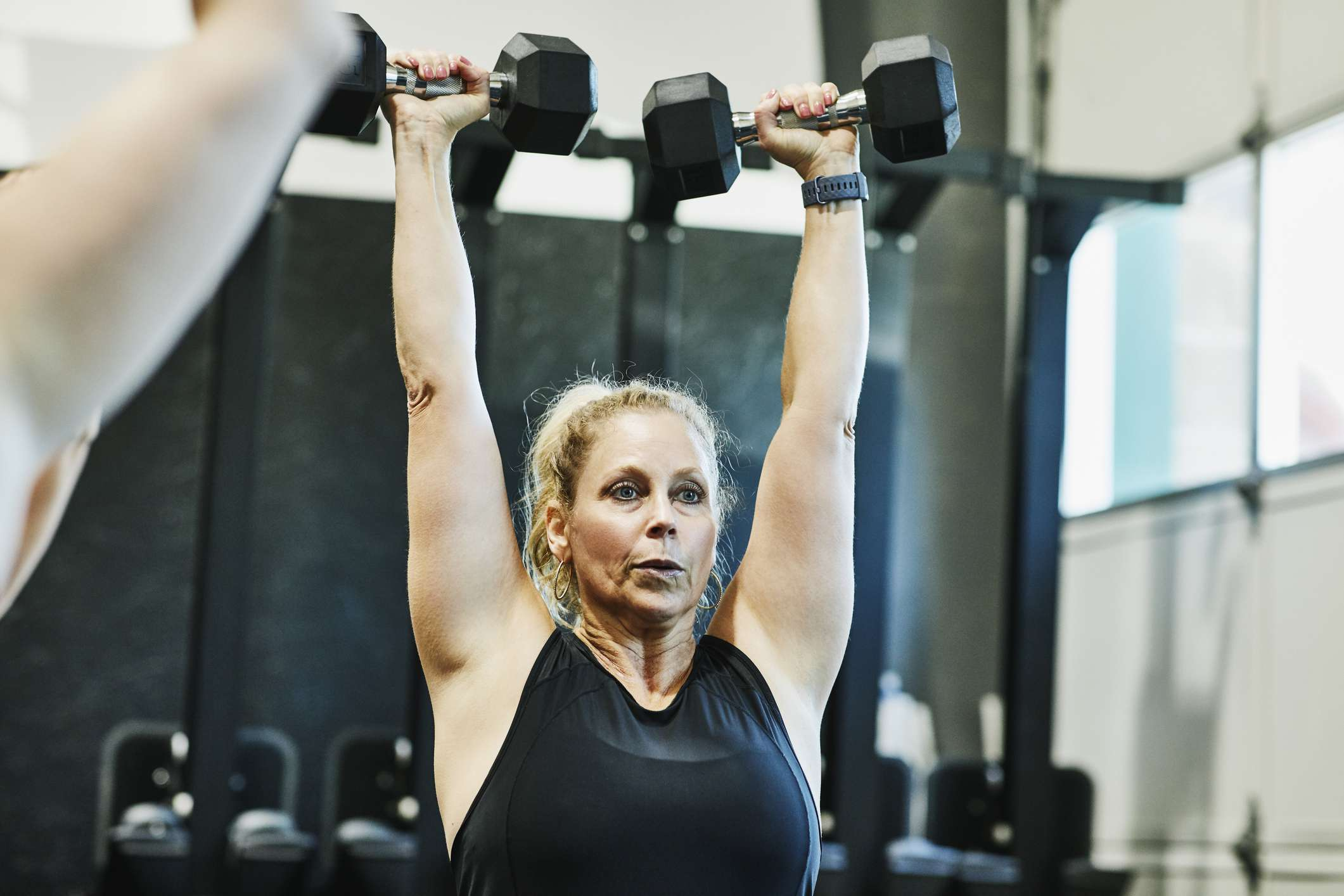Woman doing overhead dumbbell press during fitness class in gym