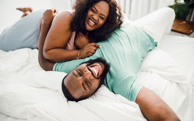 Laughing couple on the white bed stock photo