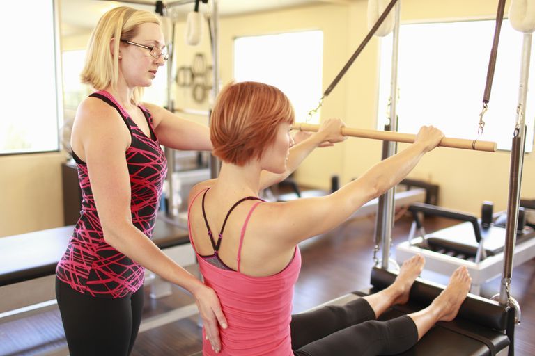 Instructor helping woman on the Pilates reformer