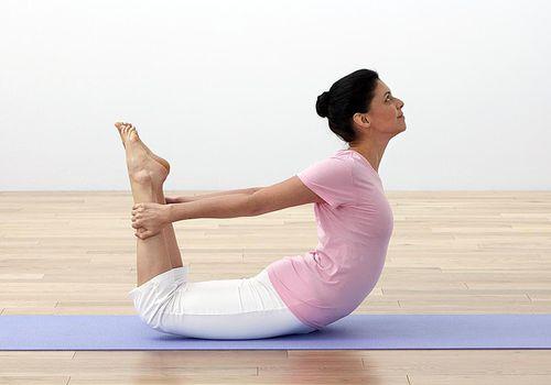 Mujer realizando pose de yoga de arco oscilante en colchoneta de ejercicios, vista lateral