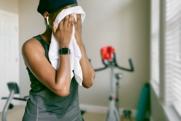 A woman wipes her face with a sweat towel in a home gym.