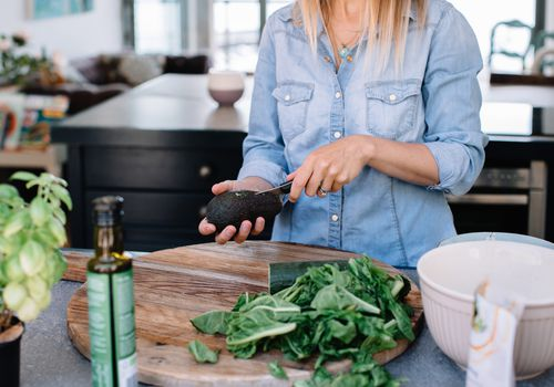 woman in her kitchen cutting avocado