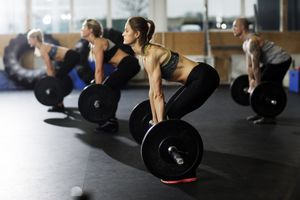Woman and man preparing to lift barbells in gym
