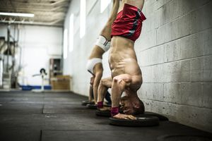 Two CrossFit athletes performing handstand push-ups against a wall.