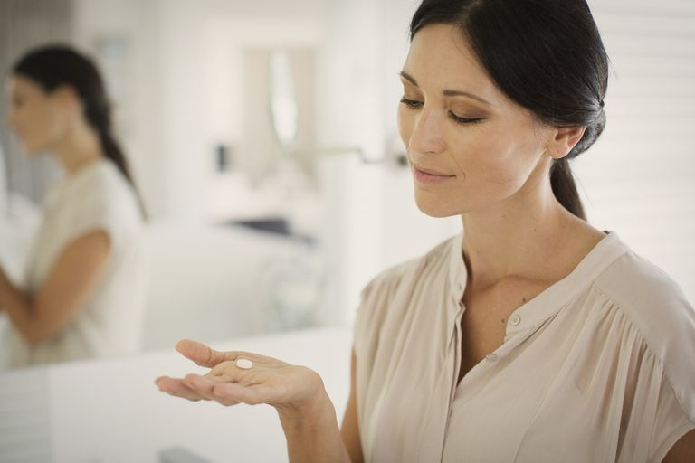 Woman with probiotic pill in hand